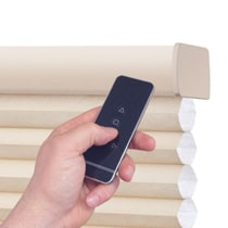 Hand holding remote for motorized shades